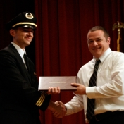 Jeremy Criddle receives his award from First Officer Logan Case