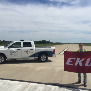 Student displays EKU banner on airport runway